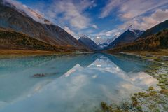 View from lake Akkem on mountain Belukha near board between Russia and Kazahstan during golden autumn. Belukha Mountain covered with snow is reflected in a royalty free stock photo