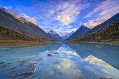 View from lake Akkem on mountain Belukha near board between Russia and Kazahstan during golden autumn. Belukha Mountain covered with snow is reflected in a stock photos