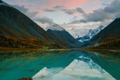 View from lake Akkem on mountain Belukha near board between Russia and Kazahstan during golden autumn. Belukha Mountain covered with snow is reflected in a stock photography
