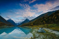 View from lake Akkem on mountain Belukha near board between Russia and Kazahstan during golden autumn. Belukha Mountain covered with snow is reflected in a royalty free stock images