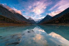 View from lake Akkem on mountain Belukha near board between Russia and Kazahstan during golden autumn. Belukha Mountain covered with snow is reflected in a stock photo