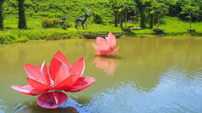 View of lake with artificial flowers in tropical tourist park. Closeup panorama of lake with artificial large pink and red flowers in tropical tourist park with stock footage