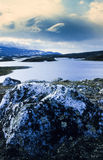 View of lake from the banks. A view of a serene lake location in the Dovre-Sunndalsfjella National Park, Dovrefjell, Norway. The rocks have white specks in them Stock Images