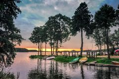 View on the lake fishing harbor with boats parked on the shore during sunset. Royalty Free Stock Photo