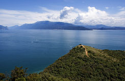View on the lake Garda and the Alpes. View on the lake Garda, the Alpes mountains and small island, Italy Stock Image