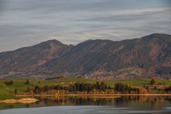 View of lake,green meadow,mountains and cloudy sky Royalty Free Stock Photo