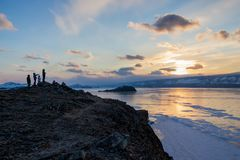 View of lake with ice surface and rocks formations with people standing on shore on sunset, russia,. Lake baikal stock images