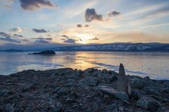 View of lake with ice surface and rocks formations on shore on sunset ,russia, lake. Baikal stock image