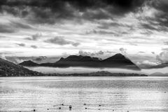 View of the lake Maggiore with stormy clouds. Black and white photo Royalty Free Stock Photos