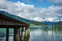 View of the lake near St. Wolfgang with a wooden pier and Alps m. Ountains background, under a blue sky with clouds on a sunny day royalty free stock image