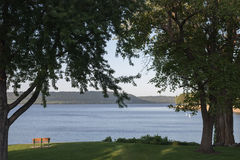 View of Lake Pepin. Park bench on beautiful Lake Pepin, viewed between trees on either side Royalty Free Stock Photo
