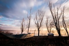 View of a lake shore with some little fishing boats, trees and warm and soft sunset colors. View of a lake shore with some little fishing boats trees and warm royalty free stock photo