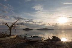 View of a lake shore at almost sunset, with some empty boats, a. Skeletal tree and two islands in the background Stock Photography