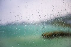 View of the lake through a window with wet glass. Blurred view of the lake seen through a window with sharp drops on a rainy day Royalty Free Stock Image