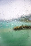 View of the lake through a window with wet glass. Blurred view of the lake seen through a window with sharp drops on a rainy day Royalty Free Stock Photography