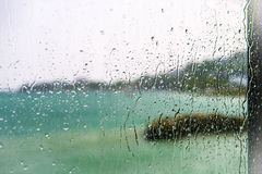 View of the lake through a window with wet glass. Blurred view of the lake seen through a window with sharp drops on a rainy day Stock Images