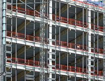 View of a large building development under construction with steel framework and girders supporting the metal floors with safety f royalty free stock photos