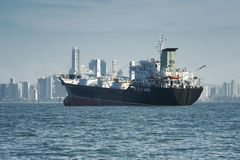 View of a large cargo ship anchored and the city skyline at the background Royalty Free Stock Photo