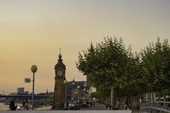 View of the large clock from the nearby footbridge in the area of Rheinwerft, Dusseldorf, Germany at dusk. View of the large clock from the nearby footbridge in royalty free stock images