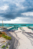 View of large fishing nets on a seashore with ocean and boats on the background Stock Photos