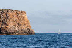 View on a large rock and a sailboat at sea Royalty Free Stock Image