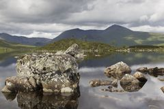 A view of Large rocks. Jutting out of the tranquil reflective waters Loch Treig in Rannnoch Moor with Scottish mountain Black Mount, AM Monadh Dubh in the stock photography
