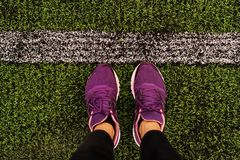 View of the legs from above in lilac sneakers on a football fiel. D Royalty Free Stock Photo