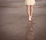 View of legs and bare feet. Girl walking along the ocean beach. View of legs and bare feet Stock Photo