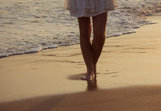 View of legs and bare feet. Girl walking along the ocean beach. View of legs and bare feet Stock Photography