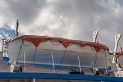 Lifeboat installed on passenger liner deck. View of Lifeboat installed on passenger liner deck in front of cloudy sky stock photography
