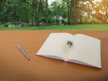 View of light bulb notebook and pencil on wooden table with green tree background royalty free stock photo