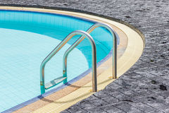 View of a light clear blue swimming pool with steel ladder. Stock Photos