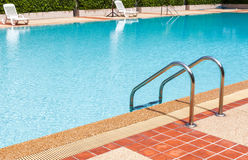 A view of a light clear blue swimming pool with steel ladder Stock Photos