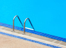 A view of a light clear blue swimming pool with steel ladder. Royalty Free Stock Image