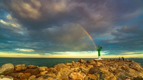 View of the lighthouse at the entrance to Port Saplaya Bay during a colorful sunset. Valencia.  Royalty Free Stock Photography