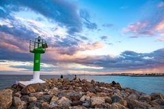 View of the lighthouse at the entrance to Port Saplaya Bay during a colorful sunset. Valencia.  Royalty Free Stock Photo