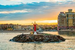 View of the lighthouse at the entrance to Port Saplaya Bay during a colorful sunset. Valencia.  Stock Photography