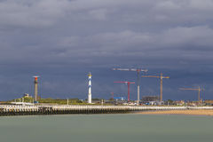 View on lighthouse and modern construction cranes against stormy sky in Ostend, Belgium Royalty Free Stock Photo