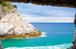 View of Ligurian sea water and rock cliff of Palmaria island through brick stone wall window of Portovenere. Coastal town, Riviera di Levante, National park royalty free stock images