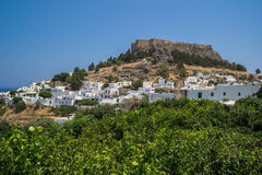 View for a Lindos City and the bay at Rhodes Island. Above the modern town rises the acropolis of Lindos, a natural citadel which was fortified successively by Stock Images