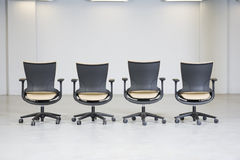 View of a line of empty office chairs. View of facing line of empty black office chairs in a white room royalty free stock photo