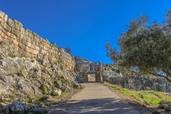 View of Lions Gate at ancient Mycenae Greece from down the hill showing the sidewalk - shaded by an olive tree - leading through stock images