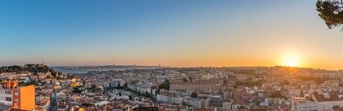 Panomaric view over Lisbon on sunset. View of Lisbon town rooftops and tejo river from the Senhora do Monte viewpoint in Graca stock photos