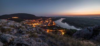 View of Lit Small City with River from the Hill at Sunset Stock Photos