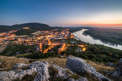 View of Lit Small City with River from the Hill at Sunset Royalty Free Stock Photography
