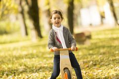 Little girl riding bicycle in autumn park. View at little girl riding bicycle in autumn park royalty free stock image