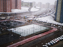 View on a living district in snow. View on a residential district, sports field, and local apartment's buildings while snow falls Royalty Free Stock Photography