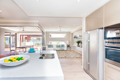 View of a living room and an exterior patio from the modern kitc. The interior of the luxury house, including kitchenware, white counter top table with fruit on Royalty Free Stock Photography