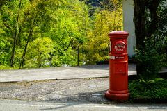 View of local red postbox standing on local street with green plant, tree and fresh light green bamboo background in Kurokawa. Onsen town, Japan Royalty Free Stock Photo