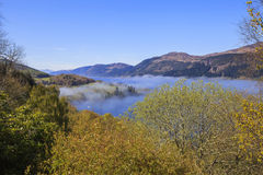 View of Loch Ness in foggy morning haze. Landscape view of Loch Ness in foggy morning haze. Fog over the lake adding mystic atmosphere to the picture.  Scotland Royalty Free Stock Image
